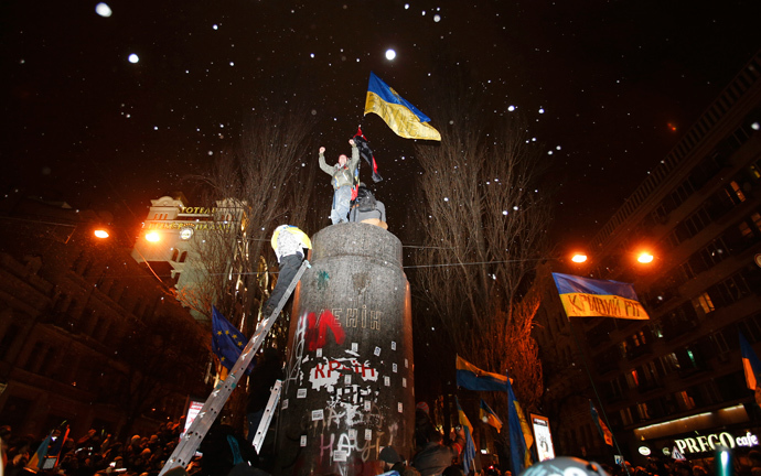 People climb up to the top of a pedestal after a statue of Soviet state founder Vladimir Lenin was toppled by protesters during a rally organized by supporters of EU integration in Kiev, December 8, 2013. (Reuters / Stoyan Nenov)