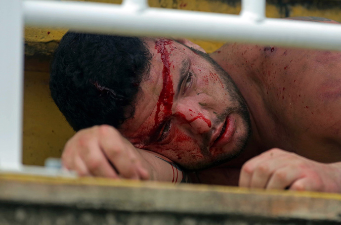 A fan of Parana's Atletico PR lies injured after being hit by fans of Rio de Janeiro's Vasco da Gama, during a Brazilian Championship football match in Joinville, Santa Catarina, on December 8, 2013. (AFP Photo / Heuler Andrey)