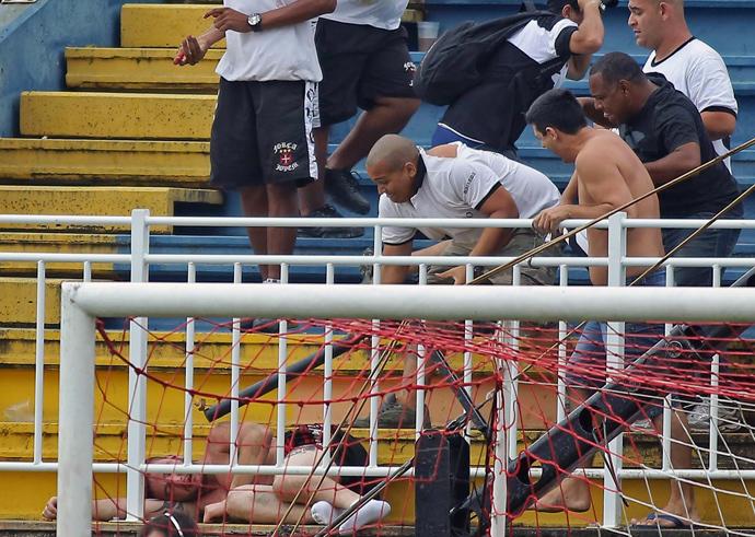 Fans of Rio de Janeiro's Vasco da Gama attack a fan of Parana's Atletico PR, during a Brazilian Championship football match in Joinville, Santa Catarina, on December 8, 2013. (AFP Photo / Heuler Andrey)