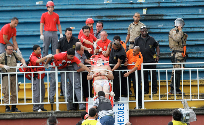 Paramedics use a stretcher to carry an injured Atletico Paranaense fan after clashes between fans of Vasco da Gama and Atletico Paranaense during their Brazilian championship match in Joinville in Santa Catarina state December 8, 2013.(Reuters / Carlos Moraes / Agencia O Dia)