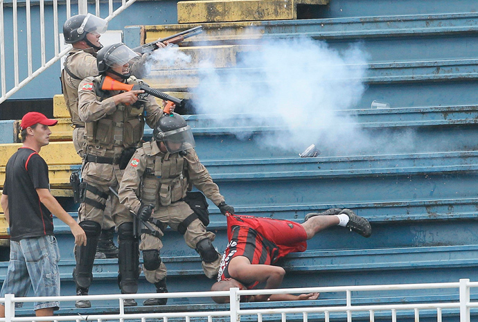 Policemen fire rubber bullets as they help an Atletico Paranaense fan during clashes between Vasco da Gama soccer fans and Atletico Paranaense fans at their Brazilian championship match in Joinville in Santa Catarina state December 8, 2013. (Reuters / Carlos Moraes / Agencia O Dia)