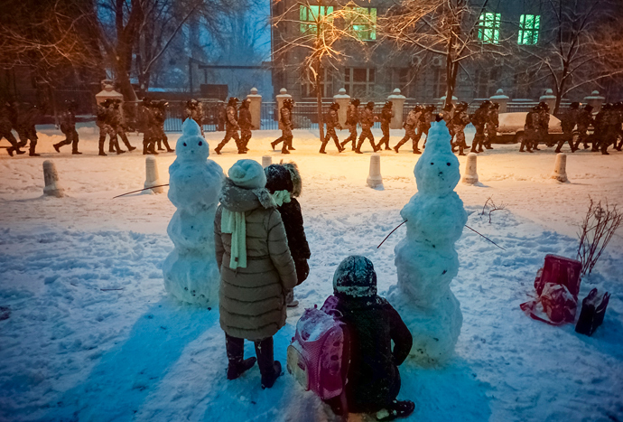 Children look on as riot police go to block a street near the presidential administration building during a gathering of supporters of EU integration in Kiev, December 9, 2013 (Reuters / Mykhailo Petiakh)