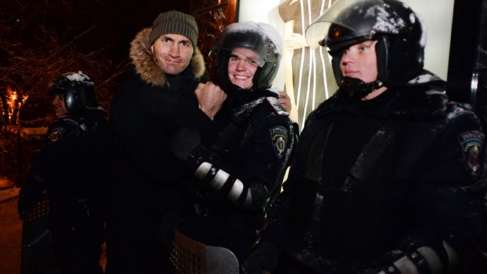 Ukrainian heavyweight boxing world champion and opposition party UDAR member Wladimir Klitschko (L) poses with police officers at a barricade in Kiev on December 9, 2013 (AFP Photo / Vasily Maximov)