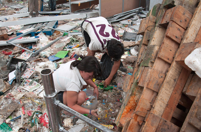 Residents look for goods amid a ransacked shop after it was looted in the northern Argentine province of Tucuman December 10, 2013. (Reuters / Paloma Cortes Aysua)