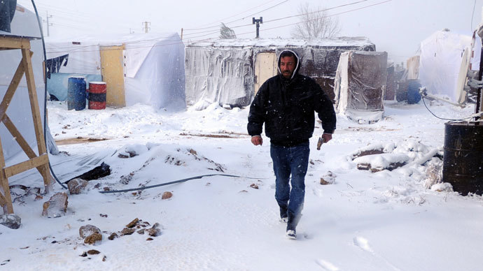 A man walks with a hammer after fixing plastic covers on tents in the snow-covered makeshift refugee camp of Terbol near the Bekaa Valley town of Zahleh in eastern Lebanon on December 11, 2013. (AFP Photo / STR)