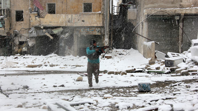 A rebel fighter aims his weapon as he stands amidst snow during clashes with Syrian pro-government forces in the Salaheddin neighbourhood of Syria's northern city of Aleppo on December 11, 2013.(AFP Photo / Medo Halab)