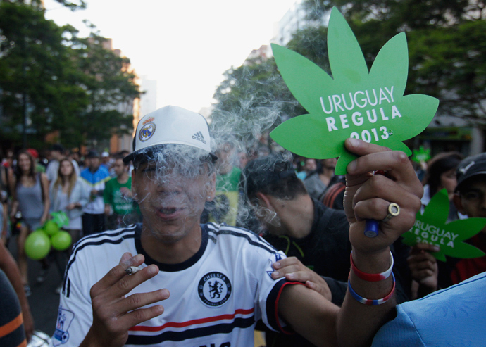 "People participate in the so-called ""Last demonstration with illegal marijuana"" on their way to the Congress building in Montevideo, as Senate debates a government-sponsored bill establishing state regulation of the cultivation, distribution and consumption of marijuana during a session, December 10, 2013. (Reuters / Andres Stapff )"