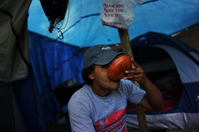 Rafael Santiago, who is homeless and works as a day laborer, takes a drink outside of the tent encampment where he lives in Waterbury, Connecticut. (Spencer Platt / Getty Images / AFP)
