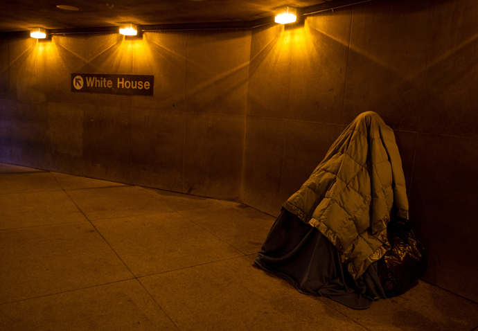 A homeless person covered in blankets for warmth, sleeps at the entrance of a Metro station near the White House in Washington, DC. (AFP Photo / Karen Bleier)