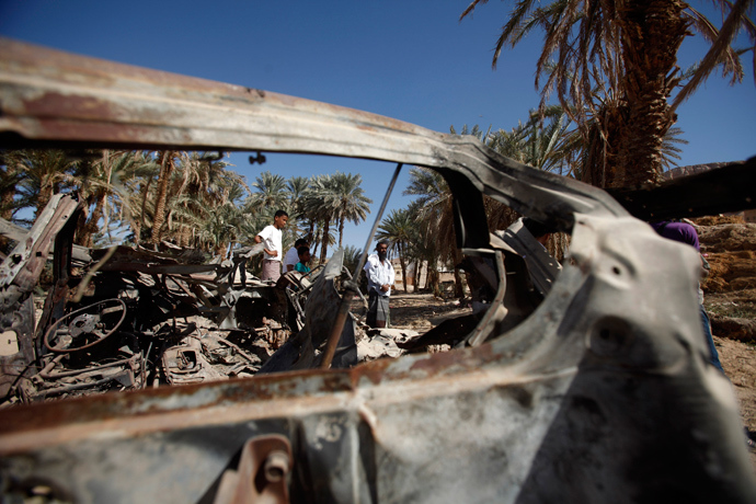 People gather near the wreckage of a car destroyed by a U.S. drone air strike that targeted suspected al Qaeda militants in August 2012, in the al-Qatn district of the southeastern Yemeni province of Hadhramout February 5, 2013 (Reuters / Khaled Abdullah)