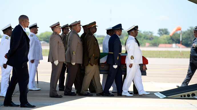 The coffin of South African former president Nelson Mandela is carried by officers as Mandela's grandson Mandla (2L) looks on after a Farewell Service on December 14, 2013 at the Waterkloof air force base in Pretoria before its departure to Mthatha (AFP Photo / Stephane De Sakutin)