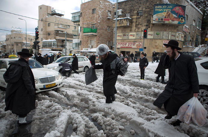 Ultra-orthodox Jews walk in a street of Jerusalem on December 13, 2013 following a snowstorm.(AFP Photo / Menahem Kahana)