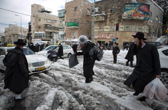 Ultra-orthodox Jews walk in a street of Jerusalem on December 13, 2013 following a snowstorm.(AFP Photo / Menahem Kahana)