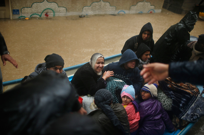 Members of a Palestinian family travel on a boat after being evacuated from their house which was flooded with rainwater on a stormy day in the northern Gaza Strip December 14, 2013. (Reuters / Mohammed Salem)