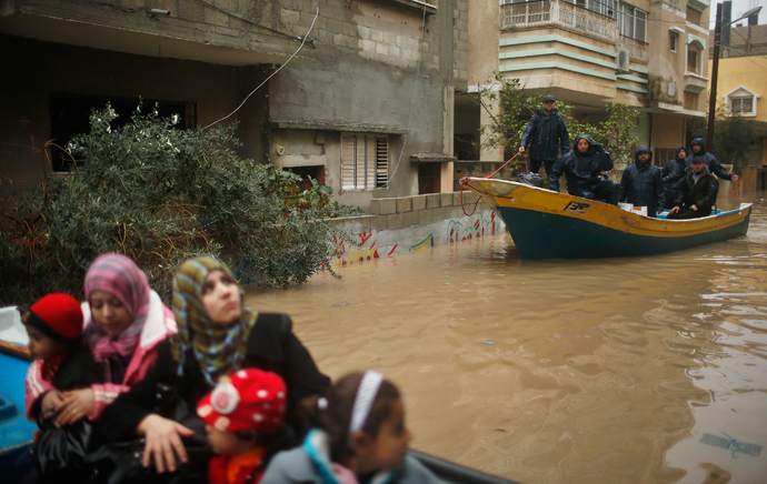 Palestinian policemen loyal to Hamas ride a boat as members of a Palestinian family travel on a boat after being evacuated from their house that is flooded with rainwater on a stormy day in the northern Gaza Strip December 14, 2013. (Reuters / Mohammed Salem)