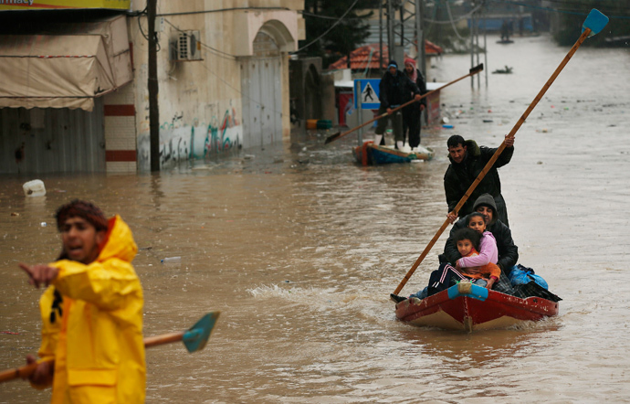 A member of the Palestinian civil defense paddles a boat as he evacuates a man and his children after their house was flooded with rainwater on a stormy day in the northern Gaza Strip December 14, 2013. (Reuters / Mohammed Salem)