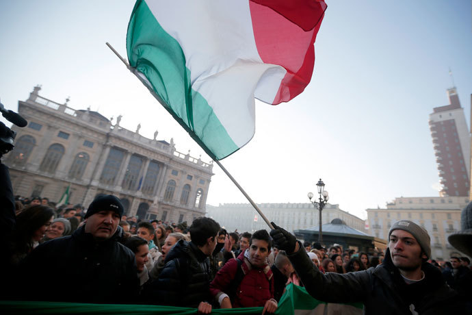 "A man waves an Italian national flag during a protest against austerity measures in ""Piazza Castello"", in Turin on December 11, 2013. (AFP Photo / Marco Bertorello)"