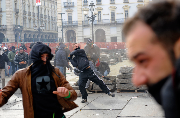 A protester throws a stone during a protest in downtown Turin December 9, 2013. (Reuters / Stringer)