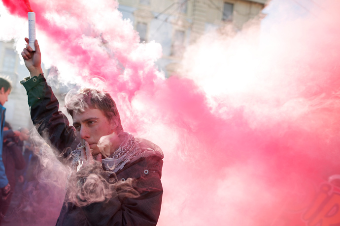 A man holds a smoke bomb during a protest by students against the local government in downtown Turin on December 14, 2013. (AFP Photo / Marco Bertorello)