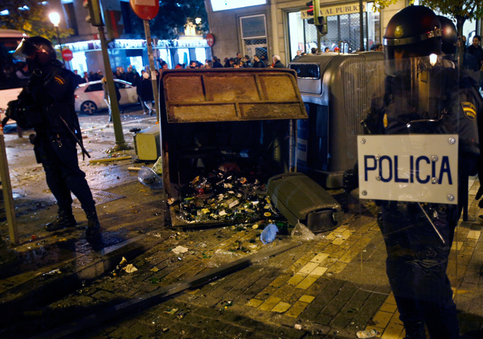 Spanish National Police officers in full riot gear stand near a trash container with broken glass bottles during clashes with protesters at the end of a protest against a new security law in Madrid December 14, 2013. (Reuters / Sergio Perez)