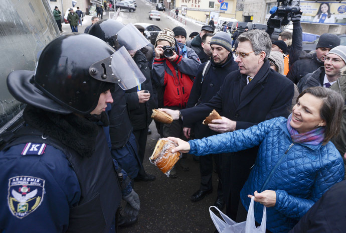 A handout picture released on December 10, 2013 by Ukrainian Union Opposition press services hows US Assistant secretary of State for European and Eurasian Affairs Victoria Nuland (R) distributing cakes to riot policemen on the Independence Square in Kiev on December 10, 2013. (AFP Photo/Andrew Kravchenko)