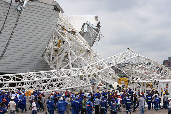 Workers stare at damages after a crane fell across part of the metallic structure at the Arena de Sao Paulo --Itaquerao do Corinthians-- stadium, still under construction, on November 27, 2013 in Sao Paulo. (AFP Photo / Lancepress - Eduardo Viana)