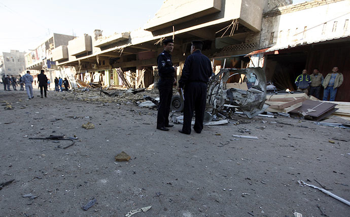 Iraqi policemen inspect the site of car bomb attack in Baghdad December 16, 2013. (Reuters / Ahmed Saad)