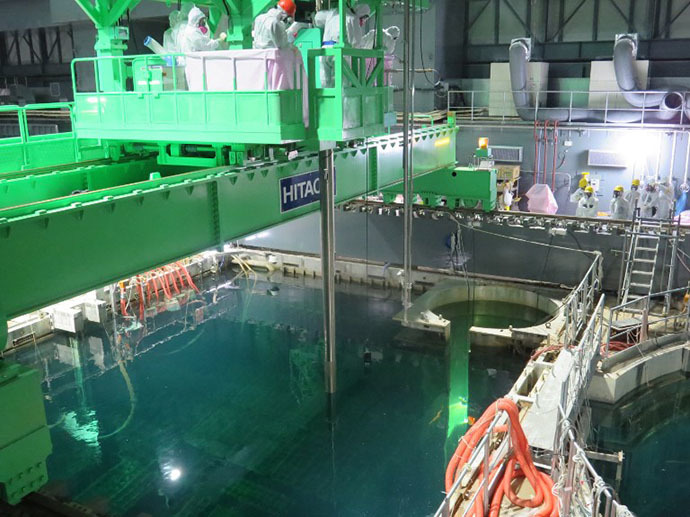 This handout picture taken by Tokyo Electric Power Co (TEPCO) on November 18, 2013 shows an operation of nuclear fuel being lifted and moved by TEPCO workers as TEPCO started operation to remove fuel rods from a pool at the unit four reactor building of TEPCO's Fukushima Dai-ichi nuclear plant in the town of Okuma in Fukushima prefecture. (AFP Photo)