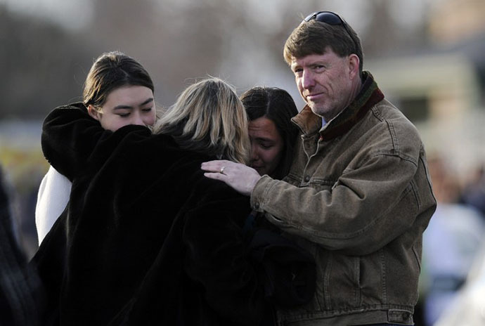 Family and friends comfort each other outside Shepherd of the Hills Church after a school shooting at Arapahoe High School on December 13, 2013 in Centennial, Colorado. (AFP Photo / Chris Schneider)
