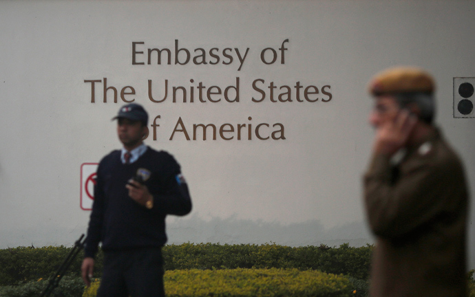 A U.S. embassy security guard (L) and an Indian policeman stand in front of the main gate of the embassy as the bulldozer (unseen) removes the security barriers, in New Delhi December 17, 2013 (Reuters / Adnan Abidi)