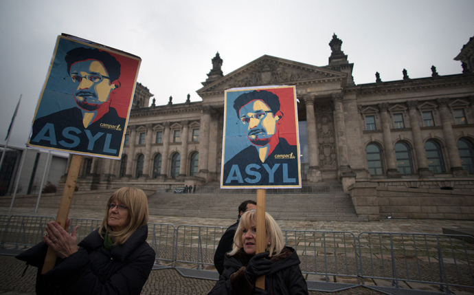Protesters hold up pictures of US whistleblower Edward Snowden in front of the Reichstag building housing the Bundestag (lower house of parliament) in Berlin on November 18, 2013 (AFP Photo / Johannes Eisele)