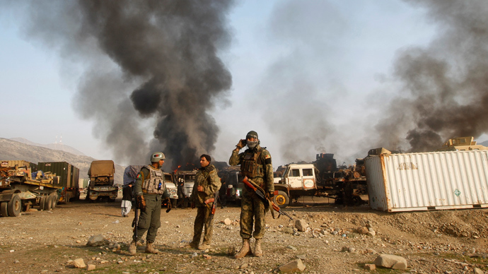 Afghan security forces stand near burning NATO supply trucks after what police officials say was an attack by militants in the Torkham area near the Pakistani-Afghan border in Jalalabad Province December 18, 2013 (Reuters / Parwiz)