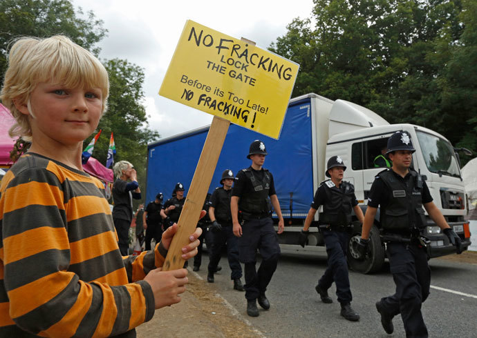 Local resident Joss Parker joins demonstrators as police escort a lorry to the entrance of a drill site run by Cuadrilla Resources, in the village of Balcombe in southern England September 3, 2013. (Reuters / Luke MacGregor)