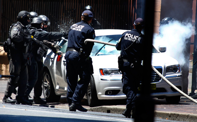 Heavily armed police officers prepare to drag a man from his car outside the New South Wales state parliament building in Sydney December 20, 2013. (Reuters / David Gray)