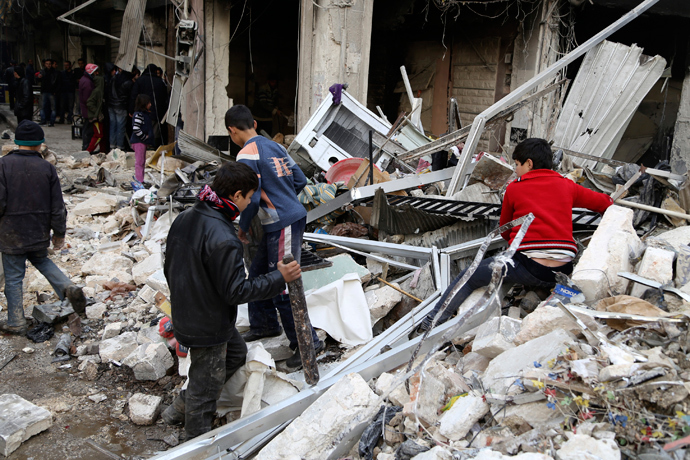 Boys are seen near debris after what activists said was an air strike from forces loyal to Syria's President Bashar al-Assad in Aleppo December 18, 2013. (Reuters / Ahmad Othman)