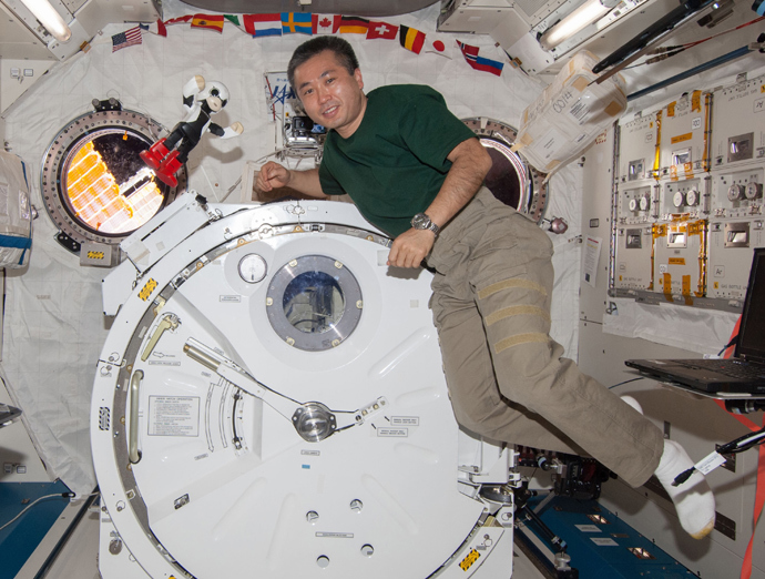 """Japanese astronaut Koichi Wakata (L) smiling with the humanoid robot """"Kirobo"""" (R) in the International Space Station (ISS) in space on December 20, 2013 (AFP Photo / KIBO Robot Project)"""