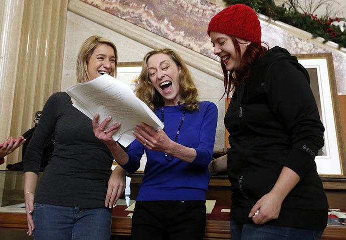 Valerie Scott (C), um dos três trabalhadores atuais e antigos do sexo que iniciaram um desafio às leis de prostituição do Canadá, reage ao ler uma cópia da decisão na Suprema Corte do Canadá, em Ottawa 20 dezembro de 2013. (Reuters / Chris Wattie)