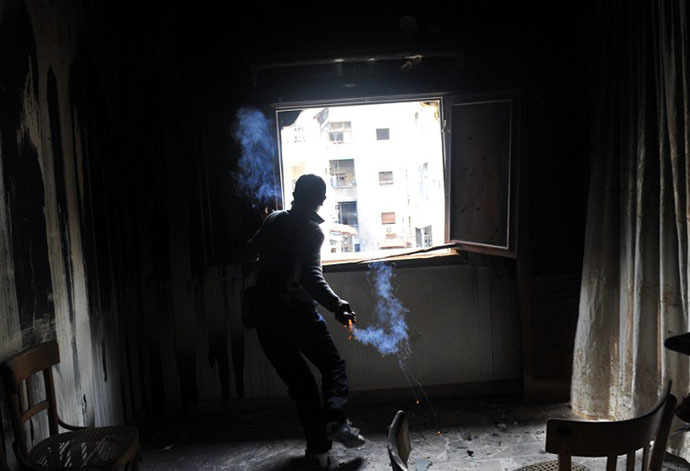 (FILES) A rebel fighter throws a homemade grenade towards Syrian government forces through a window at a flat in the Salaheddine neighbourhood of Aleppo (AFP Photo / Bulent Kilic)