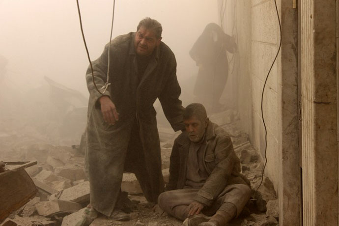 A Syrian man helps an injured man following an airstrike in Aleppo's Maadi neighborhood on December 17, 2013. (AFP Photo / Mohammed Al-Khatieb)