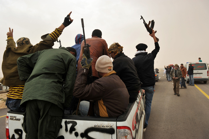 Libyan rebel fighters raise their weapons as they ride at the back of a pick-up truck on their way to battle against pro-Gaddafi forces, some 40 km down the road of the northcentral city of Ras Lanuf on March 4, 2011 (AFP Photo)