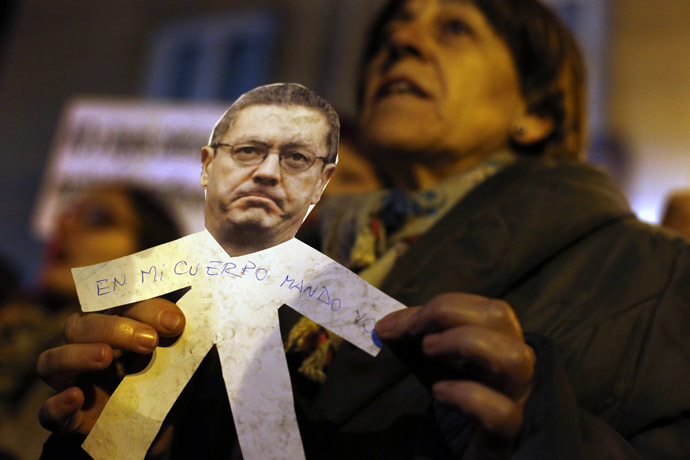 "A demonstrator holds a paper cut-out bearing the image of Spanish Justice Minister Alberto Ruiz Gallardon with the words ""I rule over my body"" written on it during a pro-choice protest against the government's proposed new abortion law in Madrid, December 20, 2013. (Reuters/Susana Vera)"