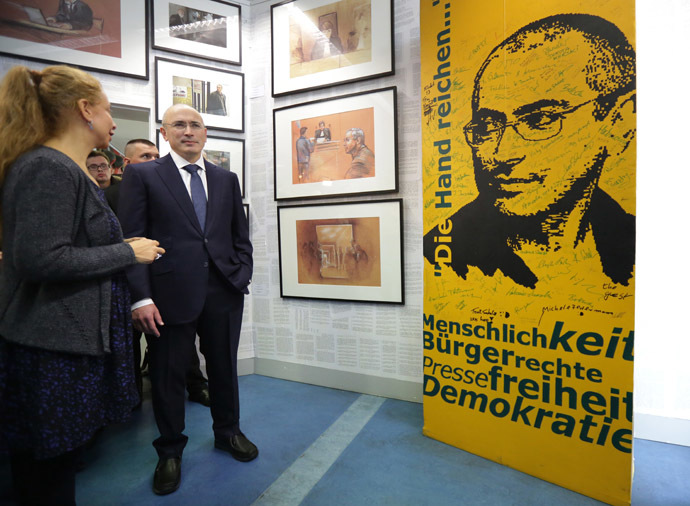 Former Russian oil tycoon and Kremlin critic Mikhail Khodorkovsky (R) and Wall Museum's director Alexandra Hildebrandt stand next to a picture of Khodorkovsky as part of the Wall Museum exhibition in Berlin on December 22, 2013. (AFP Photo/DPA)