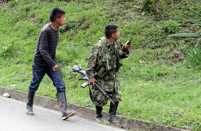 A member of the Revolutionary Armed Forces of Colombia (FARC) walks with his gun in the mountains of Caldono, Cauca province June 4, 2013.(Reuters / Jaime Saldarriaga)