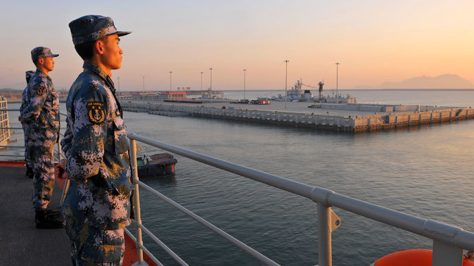 Chinese naval soldiers stand guard on China's first aircraft carrier Liaoning, as it travels towards a military base in Sanya, Hainan province, in this undated picture made available on November 30, 2013.(Reuters / Stringer)