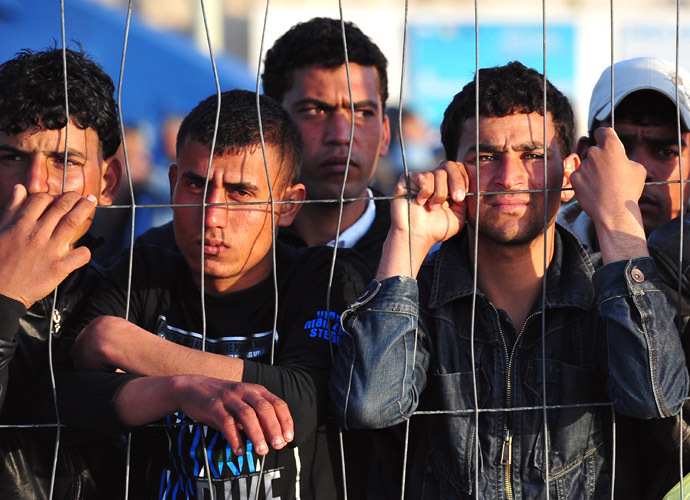 Tunisian migrants wait for the arrival of boats at Lampedusa on March 27, 2011. (AFP Photo/Alberto Pizzoli)