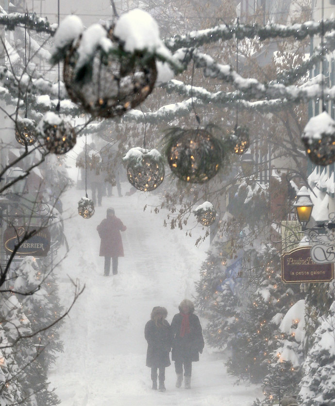 People walk in the old town during a snowstorm in Quebec City December 22, 2013. (Reuters/Mathieu Belanger)