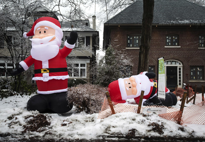 Inflatable Santa Claus decorations, one still inflated and another deflated due to a power outage, are pictured after an ice storm hit Toronto, December 22, 2013. (Reuters/Mathieu Belanger)