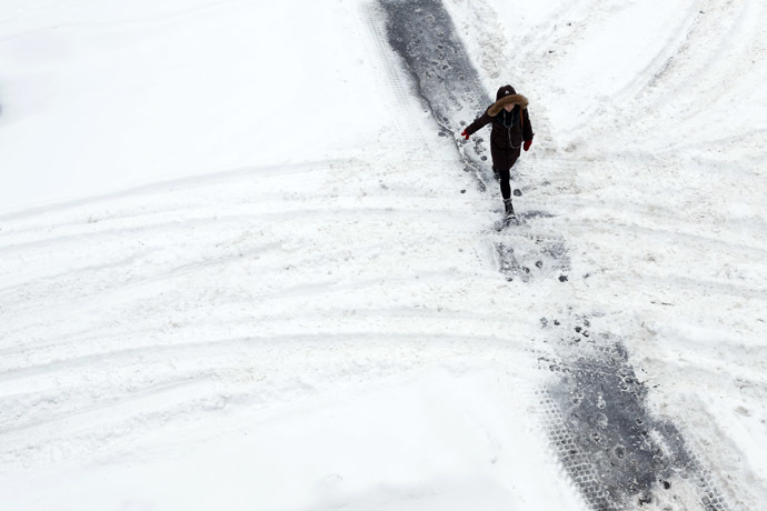 A woman walks along a path cleared in the snow while crossing a street in Ottawa December 22, 2013. (Reuters/Chris Wattie)