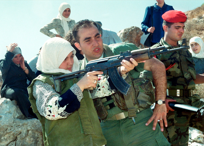 A young Palestinian woman is trained in shooting an AK-47 automatic assault rifle as she wears a protective flak jacket during a graduation exercise in a military-style summer camp held August 10, 2000 outside Nablus in the northern West Bank. (Reuters)