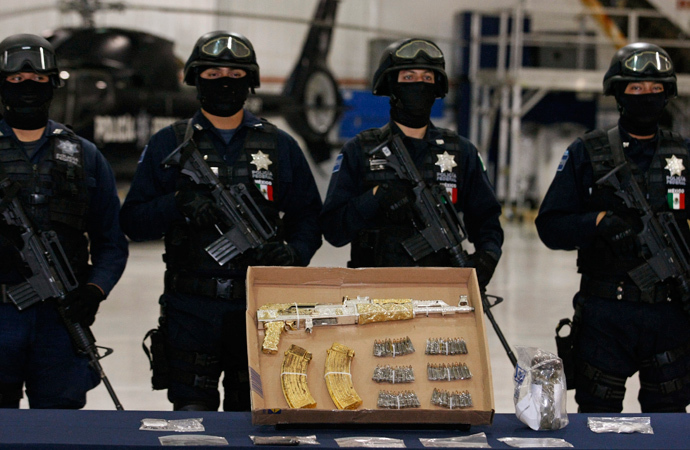 "Federal policemen stand guard behind an AK-47 rifle and ammunition, confiscated during the arrest of suspect Ramiro Pozos Gonzalez alias ""El Molca "", during a presentation to the media at the federal police headquarters in Mexico City September 12, 2012. (Reuters / Bernardo Montoya)"